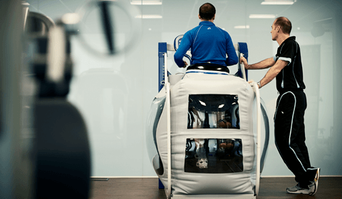 Back view of a man on an anti gravity treadmill.