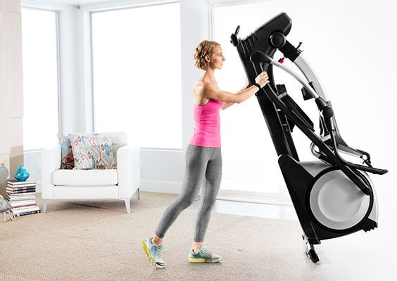 Woman with a folded elliptical trainer.