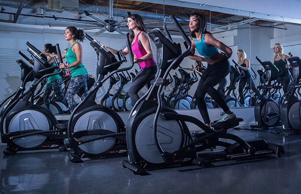People working out on an elliptical machine.