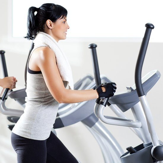 Woman working out on an elliptical machine with no hands.
